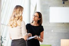 Two businesswomen having informal meeting in modern office Stock Photos