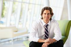 Businessman sitting on sofa in modern office Stock Photos