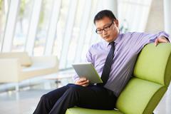 Businessman sitting in modern office using digital tablet Stock Photos