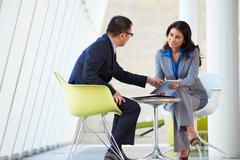 Businessman and businesswoman meeting in modern office Stock Photos