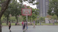 Taiwanese men playing basketball at Da-an park Stock Footage