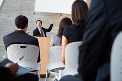Businessman delivering presentation at conference Stock Photos