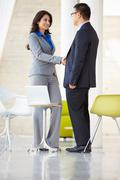 Businessman and businesswoman shaking hands in modern office Stock Photos