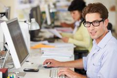 Man working at desk in busy creative office Kuvituskuvat