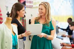 two women meeting in fashion design studio - stock photo