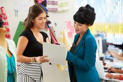 Two women meeting in fashion design studio Stock Photos