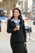 Businesswoman walking along street holding takeaway coffee Stock Photos