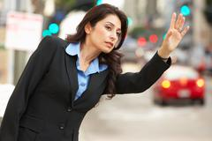 Businesswoman hailing taxi in busy street Stock Photos