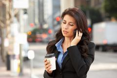 Businesswoman outside office on mobile phone Stock Photos