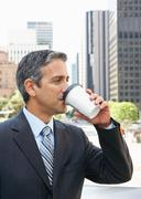 Businessman Drinking Takeaway Coffee Outside Office Stock Photos