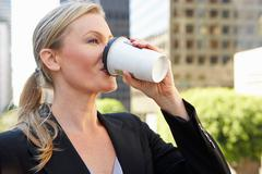 Businesswoman drinking takeaway coffee outside office Stock Photos