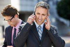businessman speaking on mobile phone in noisy surroundings - stock photo