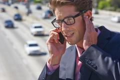 businessman speaking on mobile phone by noisy freeway - stock photo