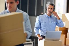 Manager using headset in distribution warehouse Stock Photos