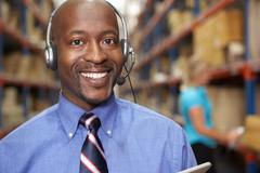 Businessman Using Headset In Distribution Warehouse Stock Photos