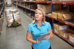 Businesswoman using digital tablet in distribution warehouse Stock Photos