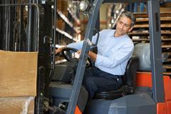 Man driving fork lift truck in warehouse Kuvituskuvat