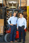 Portrait of businessmen with fork lift truck in warehouse Kuvituskuvat