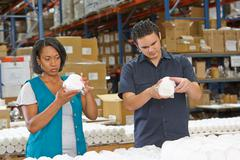 Factory workers checking goods on production line Stock Photos