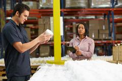 Factory worker and manager checking goods on production line Stock Photos