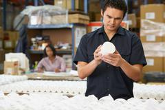 Factory worker checking goods on production line Stock Photos