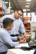 business colleagues working at desk in warehouse - stock photo