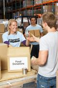 Volunteers Collecting Food Donations In Warehouse Stock Photos