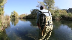 fly fisherman catching trout in river - stock footage