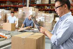 Worker using tablet computer in distribution warehouse Stock Photos