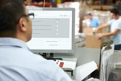 Person at computer terminal in distribution warehouse Stock Photos