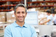 Man at computer terminal in distribution warehouse Stock Photos