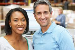 Two workers at computer terminal in distribution warehouse Stock Photos