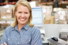 Woman at computer terminal in distribution warehouse Stock Photos