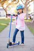 Girl wearing safety helmet riding scooter Stock Photos