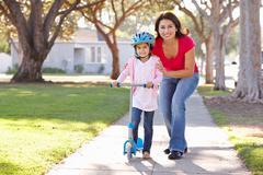 Mother teaching daughter to ride scooter Stock Photos