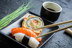 sushi in a black ceramic eaten with chopsticks - stock photo