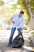 Man picking up litter in suburban street Stock Photos