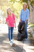 Mother and daughter picking up litter in suburban street Stock Photos