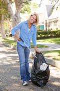 Woman picking up litter in suburban street Stock Photos