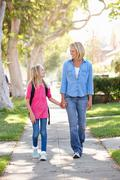 Mother and daughter walking to school on suburban street Stock Photos