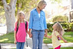 Mother and daughters walking to school on suburban street Stock Photos