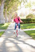 Girl wearing rucksack cycling to school Stock Photos