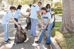 Team of volunteers picking up litter in suburban street Stock Photos