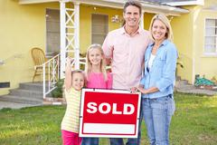 Family Standing By Sold Sign Outside Home Stock Photos
