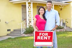 Couple Standing By For Rent Sign Outside Home - stock photo