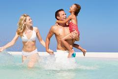 Family having fun in sea on beach holiday Stock Photos