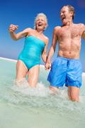 Senior couple having fun in sea on beach holiday Stock Photos
