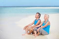 Senior couple in sports clothing relaxing on beautiful beach Stock Photos