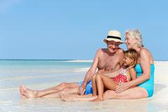 Grandparents with granddaughter enjoying beach holiday Stock Photos