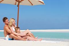 Family sitting under umbrella on beach holiday Stock Photos